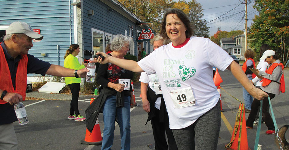 Running for Rides: Volunteer Bill Weir hands water to Ann Worrick as she crosses the finish line at the 2017 Mary Parker Memorial 5K. BHSL sponsored the event to raise money for Island Connections.